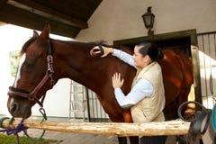Młoda kobieta pieszczotliwy koń Fotografia Stock
