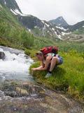 Młoda kobieta pije od strumienia z plecakiem Fotografia Stock