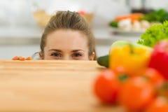 Młoda kobieta przyglądająca od tnącej deski out Obraz Stock
