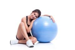 Młoda kobieta robi ćwiczeniom z sprawności fizycznej piłką Fotografia Stock
