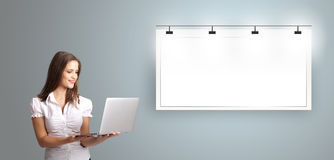 Młoda kobieta trzyma laptop i przedstawia nowożytną kopii przestrzeń Fotografia Stock
