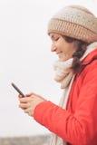 Młoda kobieta używa telefon komórkowego texting, pisać na maszynie i ono uśmiecha się, Zdjęcia Royalty Free
