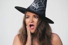 Młoda kobieta w Halloweenowym czarownica kapeluszu z zdziwioną twarzą Zdjęcia Royalty Free