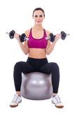 Młoda kobieta w sportach jest ubranym obsiadanie na sprawności fizycznej piłce z dumbbell Obraz Royalty Free