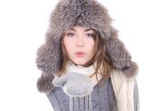 Młoda kobieta w zimy odzieżowym dmuchaniu coś od jej palm ja Zdjęcia Royalty Free