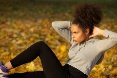 Młoda kobieta ćwiczyć siedzi podnosi outdoors Zdjęcia Royalty Free