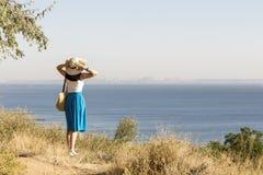 Młoda kobieta & x28; brunette& x29; w błękitnej spódnicy i kapeluszu spojrzeniach przy morzem Zdjęcie Royalty Free