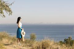 Młoda kobieta & x28; brunette& x29; w błękitnej spódnicy i kapeluszu spojrzeniach przy morzem Fotografia Stock