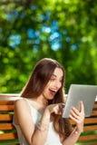 Młoda kobieta z cyfrową pastylką w parku Zdjęcia Royalty Free