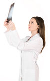 Młoda kobiety lekarka patrzeje promieniowanie rentgenowskie obrazek głowa odizolowywa Zdjęcie Royalty Free