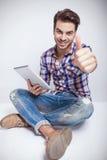Moda mężczyzna siedzący andz pokazuje aprobata gest fotografia royalty free