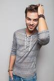 Moda mężczyzna uśmiecha się jego włosy i załatwia Fotografia Stock