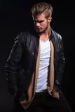 Moda mężczyzna w skórzanej kurtce jest przyglądający jego z powrotem Zdjęcia Stock