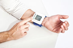 Młoda man's ręka mierzy jego ciśnienie krwi Fotografia Royalty Free