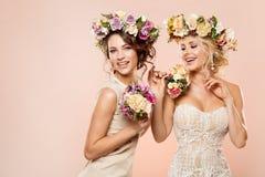 Moda modelów kwiatów fryzury piękna portret, Dwa Szczęśliwej kobiety z kwiatu wiankiem i bukiet, zdjęcia royalty free