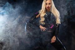 Moda model DJ i rowerzysta w hełmofonach, czarna skórzana kurtka, rzemienni spodnia, elegancka ładna blondynki kobieta w nocy fotografia royalty free