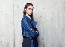Moda model jest ubranym drelichowej kurtki i długiego czerni spódnicowy pozować w studiu zdjęcia stock