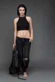 Moda model jest ubranym skór spodnia pozuje na popielatym tle kurtkę i zdjęcie royalty free
