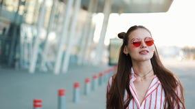 Moda model w czerwonych okularach przeciwsłonecznych chodzi ufnego wzdłuż ulicznego pobliskiego centrum handlowego młodzi dorośli zbiory
