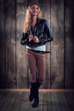 Moda model z kędzierzawym włosy ubierał w czarnej kurtce, drelichów spodniach i wysokich butach nad drewnianym ściennym tłem, Zdjęcia Royalty Free