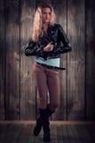 Moda model z kędzierzawym włosy ubierał w czarnej kurtce, drelichów spodniach i wysokich butach nad drewnianym ściennym tłem, Fotografia Stock