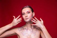 Moda modela kobieta z modnym błyskotliwość makijażem pokazuje ona gwoździe obrazy royalty free