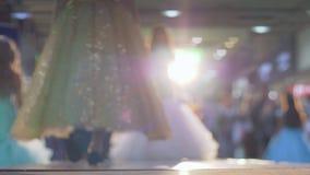 Moda modele w długich błyszczących sukniach iść wybieg w backlight na tło zamazującej widowni zbiory