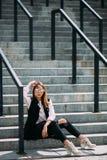 Moda modnisia chłodno dziewczyna w okularach przeciwsłonecznych miastowy tło, mody spojrzenie Wzorcowy obsiadanie na schodkach Zdjęcie Stock