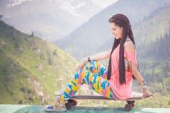 Moda nastolatka dziewczyna z longboard deskorolka przy górą Zdjęcia Royalty Free