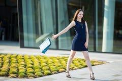Młoda nikła dziewczyna z zakupami przy ulicą Szczęśliwy Zdjęcia Royalty Free