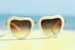 Moda okularów przeciwsłonecznych serce kształtował na koloru żółtego stojaku z błękitnym dennym tłem zdjęcie royalty free