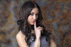 Młoda piękna brunetki kobieta stawiał forefinger wargi jako sig Fotografia Royalty Free