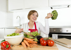 Młoda piękna domu kucharza kobieta przy nowożytnego kuchennego narządzania sałatkowego pucharu jarzynowy ono uśmiecha się szczęśl Fotografia Stock