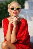 Moda portret młoda ładna blondynki dziewczyna w czerwieni sukni i su Fotografia Stock