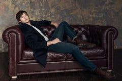 Moda portret przystojny mężczyzna w pulowerze, cajgach i jesień żakiecie na kanapie nad grunge tłem, piękny taniec para strzału k obrazy stock