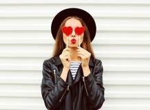 Moda portreta ładna słodka młoda kobieta z czerwonymi wargami robi lotniczemu buziakowi z lizaka czarnego kapeluszu kierową jest  Fotografia Stock