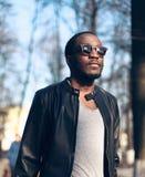 Moda portreta afrykański mężczyzna jest ubranym okulary przeciwsłonecznych, czerni rockowa skórzana kurtka na ulicie zdjęcie royalty free