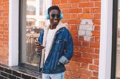 Moda portreta afrykański mężczyzna słucha muzyka na miasto ulicie z smartphone obrazy royalty free