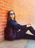 Moda portreta kobieta siedzi nad cegły tłem w czerni skały stylu Zdjęcia Royalty Free