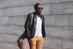 Moda portreta mężczyzna elegancki afrykański być ubranym okulary przeciwsłoneczni i czerni rockowa skórzana kurtka z torbą w mieś zdjęcie royalty free