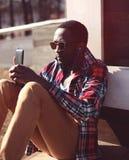 Moda portreta młody afrykański mężczyzna słucha muzyczny używa smartphone zdjęcia royalty free
