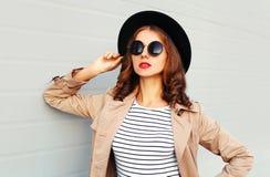 Moda portreta piękna młoda kobieta jest ubranym czarnych kapeluszy okularów przeciwsłonecznych żakiet nad popielatym tłem z czerw Fotografia Royalty Free