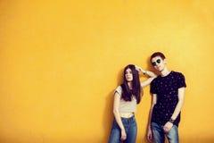 Moda que mira a los adolescentes que presentan en la pared amarilla Imagen de archivo
