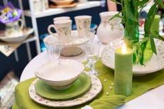 Moda servida tabla verde con glases y placas Fotos de archivo libres de regalías
