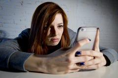Młoda smutna podatna dziewczyna używa telefon komórkowego i desperackiego cierpienia online nadużycie cyberbullying okaleczał Fotografia Stock