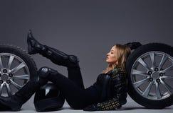 Moda, sport, ekstremum Rowerzysta dziewczyna jest ubranym motocykl przekładni lying on the beach na podłodze z samochodowym toczy zdjęcia stock