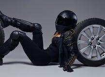 Moda, sport, ekstremum Rowerzysta dziewczyna jest ubranym motocykl przek?adni lying on the beach na pod?odze z samochodowym toczy obraz royalty free