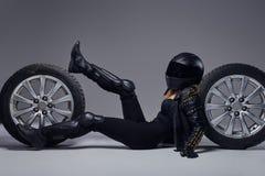 Moda, sport, ekstremum Rowerzysta dziewczyna jest ubranym motocykl przek?adni lying on the beach na pod?odze z samochodowym toczy obraz stock