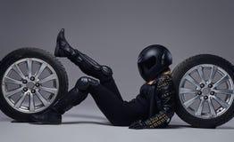 Moda, sport, ekstremum Rowerzysta dziewczyna jest ubranym motocykl przek?adni lying on the beach na pod?odze z samochodowym toczy obrazy royalty free