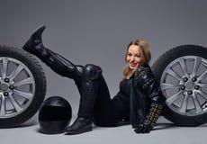 Moda, sport, ekstremum Rozochocona rowerzysta dziewczyna jest ubranym motocykl przekładni ochronnego lying on the beach na podłod zdjęcie royalty free